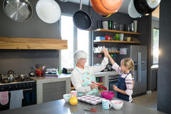 Smiling grandmother and granddaughter giving a high five. While making cupcakes in the kitchen Royalty Free Stock Images