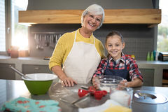 Smiling grandmother and granddaughter holding a bowl of flour in the kitchen. Close-up of smiling grandmother and granddaughter holding a bowl of flour in the Royalty Free Stock Photography