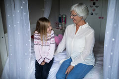 Smiling grandmother and granddaughter interacting with each other on bed Stock Images
