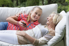 Smiling grandmother and granddaughter laying on outdoor sofa with mp3 player Stock Images