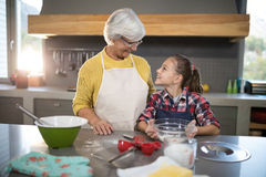Smiling grandmother and granddaughter looking at each other while holding a bowl of flour. In the kitchen Stock Photography