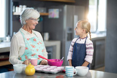 Smiling grandmother and granddaughter looking at each other stock photography