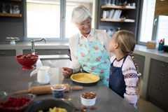 Smiling grandmother and granddaughter looking at each other while making pie. In the kitchen Royalty Free Stock Photo