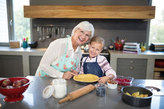 Smiling grandmother and granddaughter posing while making pie royalty free stock photos