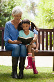 Smiling grandmother and granddaughter reading novel while sitting on wooden bench. At garden Stock Photo