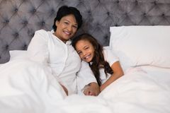 Smiling grandmother and granddaughter relaxing on bed at home. Portrait of smiling grandmother and granddaughter relaxing on bed at home Royalty Free Stock Images