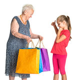 Smiling grandmother with granddaughter with shopping bags Royalty Free Stock Image
