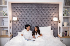 Smiling grandmother and granddaughter talking while sitting on bed Royalty Free Stock Image