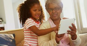 Smiling grandmother and granddaughter using digital tablet on sofa in living room 4k. Smiling grandmother and granddaughter using digital tablet on sofa in stock video