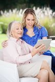 Smiling Grandmother And Granddaughter Using Tablet Royalty Free Stock Photo