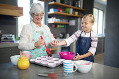 Smiling grandmother helping granddaughter while pouring cupcake batter. Into the tray Stock Photography