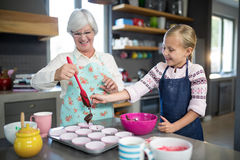 Smiling grandmother helping granddaughter while pouring cupcake batter. Into the tray Stock Photos