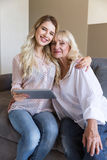 Smiling grandmother and her granddaughter holding a tablet Royalty Free Stock Photo