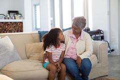 Smiling grandmother interacting with granddaughter in living room. At home Royalty Free Stock Image