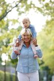 Smiling grandmother piggyback ride with baby Stock Photo