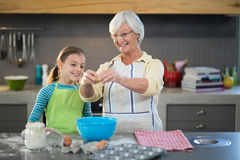Smiling grandmother showing granddaughter to break eggs. In the kitchen Royalty Free Stock Images