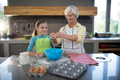 Smiling grandmother showing granddaughter to break eggs. In the kitchen Royalty Free Stock Photo