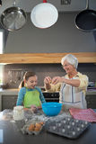 Smiling grandmother showing granddaughter to break eggs. In the kitchen Royalty Free Stock Image