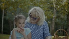 Smiling grandmother talking with cute girl in park. Portrait of loving attractive grandmother talking with her cute elementary age granddaughter in park during stock video footage