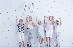 Smiling grandparents enjoying friend`s birthday. Couple holding silver balloons against white wall with gold dots stock image