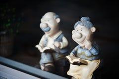 Smiling Grandparents reading book Stock Photo