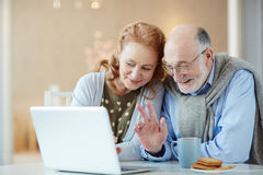 Smiling Grandparents Video chatting via Laptop n Stock Images