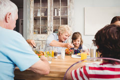 Smiling granny and granddaughter while sitting at dining table Stock Images