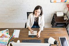 Smiling graphic designer at her desk. Top view of a beautiful female graphic designer enjoying her work and smiling stock images