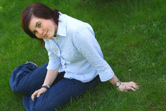 Smiling on a grass. A young smiling girl sitting on a grass Royalty Free Stock Photos
