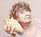 Smiling great grandmother listening. To a seashell Royalty Free Stock Image