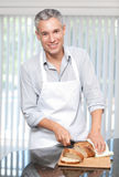 Smiling grey hair man cutting bread in apron. Attractive smiling grey hair man cutting bread in apron and cooking Stock Images
