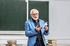 Smiling grey hair professor holding paper plane. In lecture hall royalty free stock photography