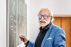 Smiling grey hair professor holding piece. Of chalk stock images