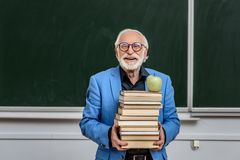 Smiling grey hair professor holding stack of books with apple. On top stock photo