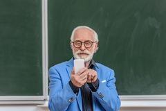 Smiling grey hair professor looking at smartphone. In lecture room stock photos
