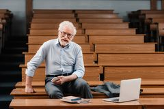 Smiling grey hair professor sitting in empty. Lecture room royalty free stock image