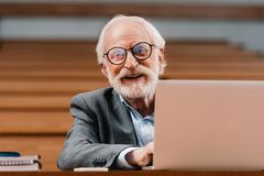 Smiling grey hair professor sitting in empty lecture room. With laptop stock photography