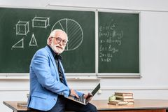Smiling grey hair professor sitting on table. With laptop stock photography