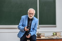 Smiling grey hair professor sitting on table. In lecture room stock image