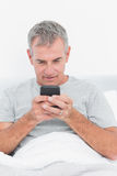 Smiling grey haired man sending a text in bed Stock Image