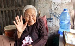Old woman in Hanoi, Vietnam. Smiling, grey haired old woman waving good-bye in Hanoi, Vietnam Royalty Free Stock Images