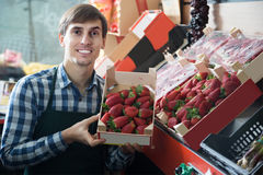 Smiling grocery worker selling fresh strawberry at market Royalty Free Stock Image