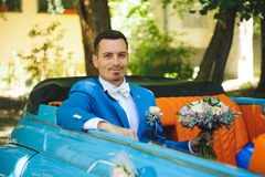 Smiling Groom with Bouquet. In blue car Stock Image