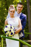 Smiling groom and bride behind handrail royalty free stock images