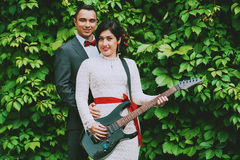 Smiling groom and bride with guitar Royalty Free Stock Images