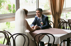 Smiling groom and bride sitting at table in restaurant Stock Photos