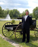 Smiling groom and carriage. Smiling groom stood in front of old carriage, countryside scene with lake in background royalty free stock photos