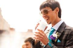 Smiling groom  drinking a soda Royalty Free Stock Photos
