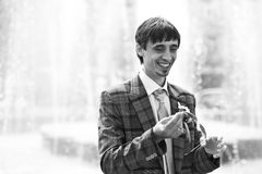 Smiling groom holding flower on the background  fountain Royalty Free Stock Images