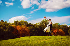 Smiling groom holding happy bride on field Stock Photography